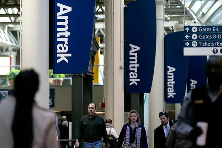 Commuters walk past Amtrak signs at Union Station in Washington, D.C., U.S., on Friday, Feb. 15, 2013. (Andrew Harrer/Bloomberg)