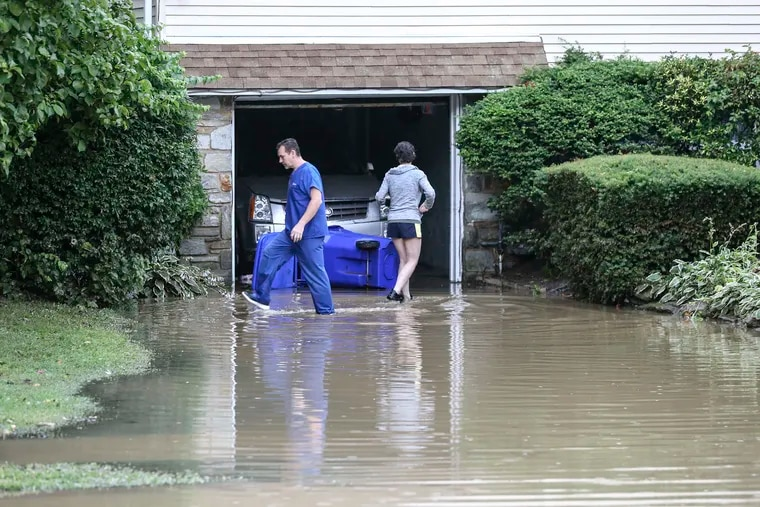 Greg and Natalie Ilin wade through a flooded driveway on Coventry Avenue in Cheltenham Township after downpours on Monday.