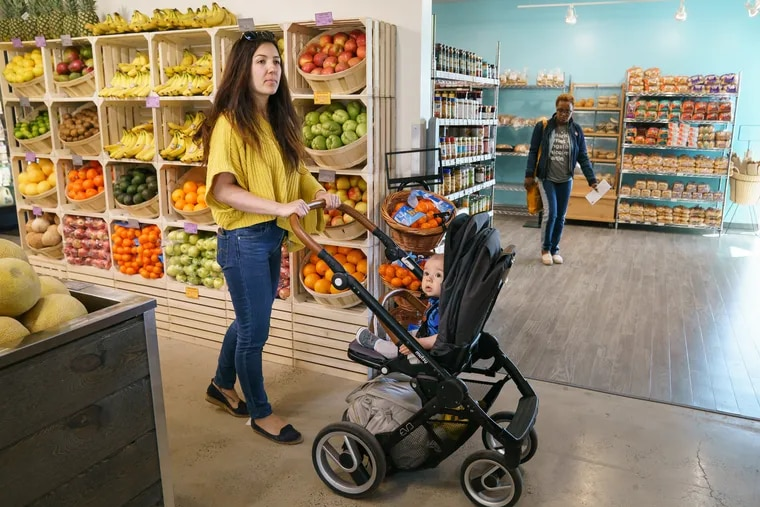 Vera Rosen shops with son Maksen Kenzou at the newly opened Kensington Community Food Co-op in Philadelphia on April 24.