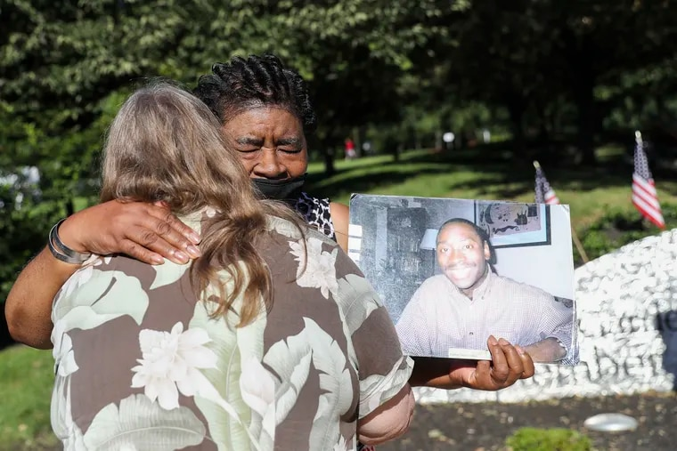 Elsie Goss Caldwell is hugged by a well-wisher as she holds a photo of her son, Kenneth Marcus Caldwell, who was 30 years old when he was killed in the 9/11 attack on the World Trade center, following a ceremony on the 20th anniversary of 9/11 at the Garden of Reflection in Lower Makefield, Pa.