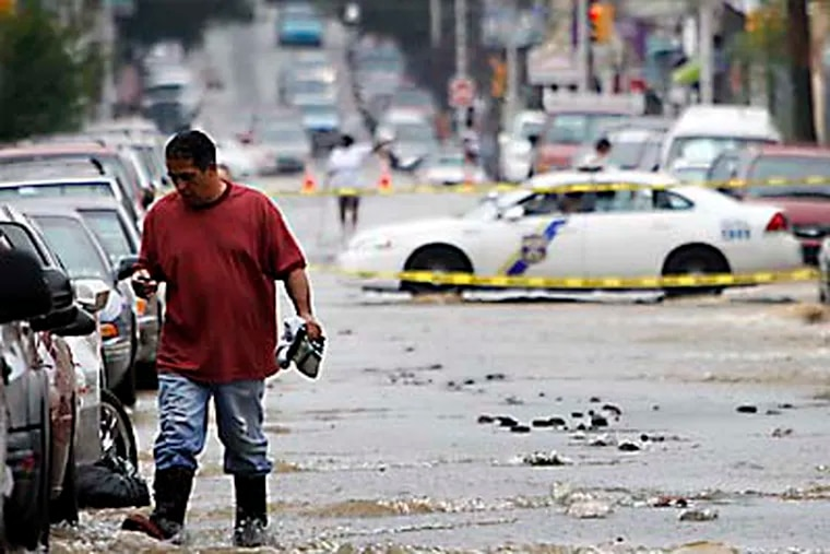 Residents near North Front and Tioga streets watch water flow down Front Street after a water main broke early Wednesday, Aug. 1, 2012. (Alejandro A. Alvarez / Staff Photographer)