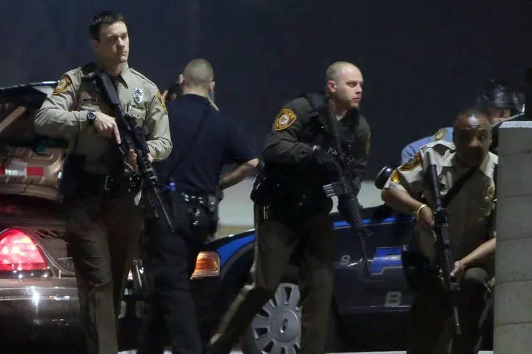 Police mobilize in the parking lot of the Ferguson police station after two officers guarding the building's front were shot. No suspects were in custody Thursday.