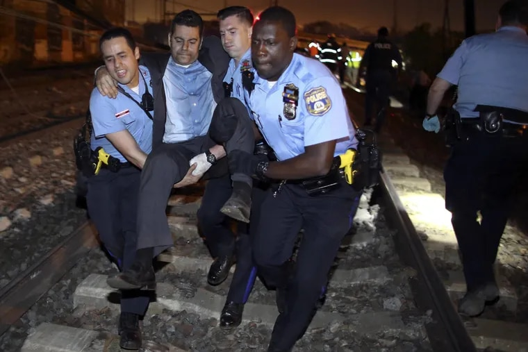 Emergency personnel help a passenger at the scene of the May 12, 2015, Amtrak derailment that killed eight people and hurt 156.