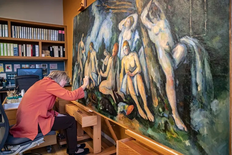 Barbara Buckley, director of conservation and chief conservator of paintings at the Barnes Foundation, removes varnish from Paul Cezanne's The Large Bathers.