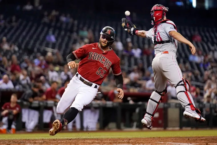 The Arizona Diamondbacks' Christian Walker scores as Phillies catcher J.T. Realmuto misses a wide throw during the fourth inning Wednesday.