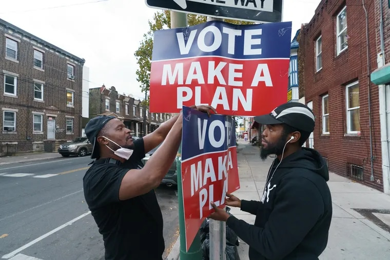 Uumar Shabazz, left, and a colleague hang a sign to promote voting on Snyder Ave. at the corner of 8th Street in Philadelphia on Oct. 7.