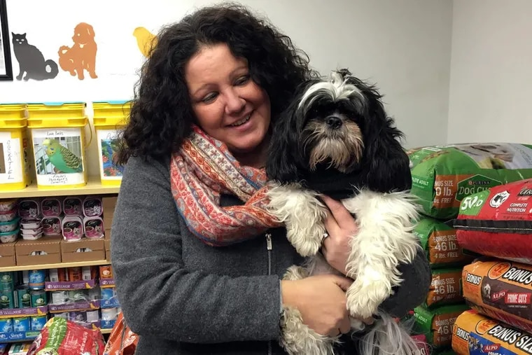 Amy Kocis, executive director of the Animal Food Bank of the Lehigh Valley, awaits clients at the food bank with her dog MoMo.
