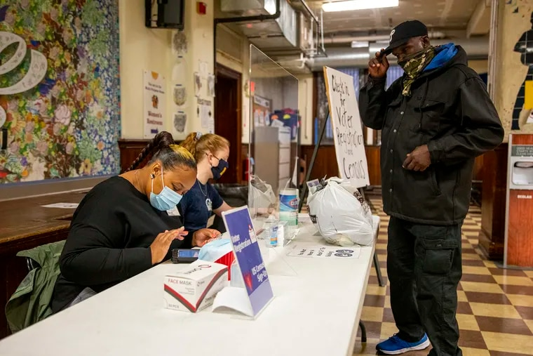 Christine Ross (left) helps James Galloway Jr. with his voter registration at Broad Street Ministry.
