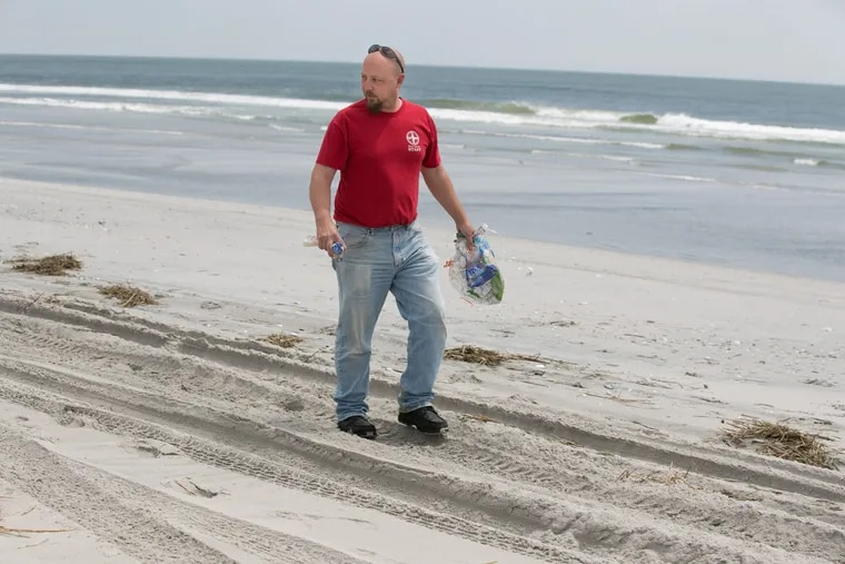 Jay Pagel, a senior field technician at the Marine Mammal Stranding Center, shown here picking up plastic on the beach, in Brigantine in May 2018.