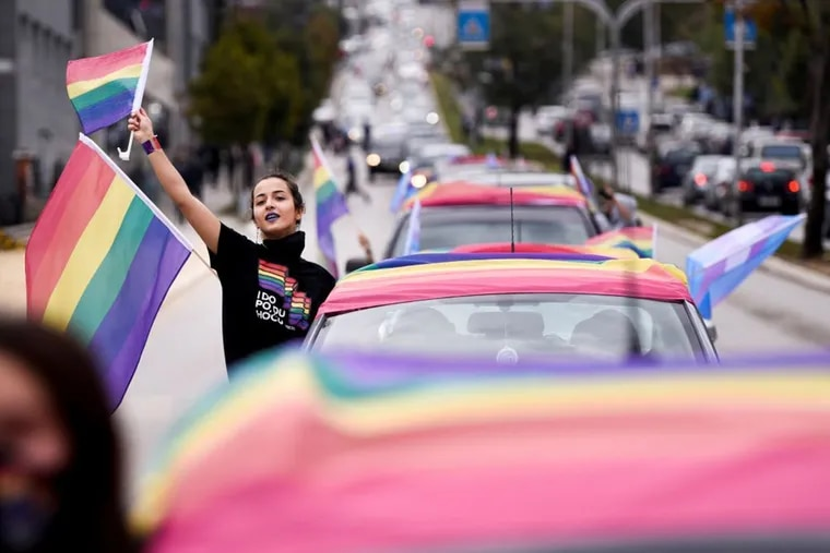A girl waves rainbow flags as she takes part in the lesbian, gay, bisexual and transgender (LGBT) Pride Parade in Pristina on October 12, 2020.
