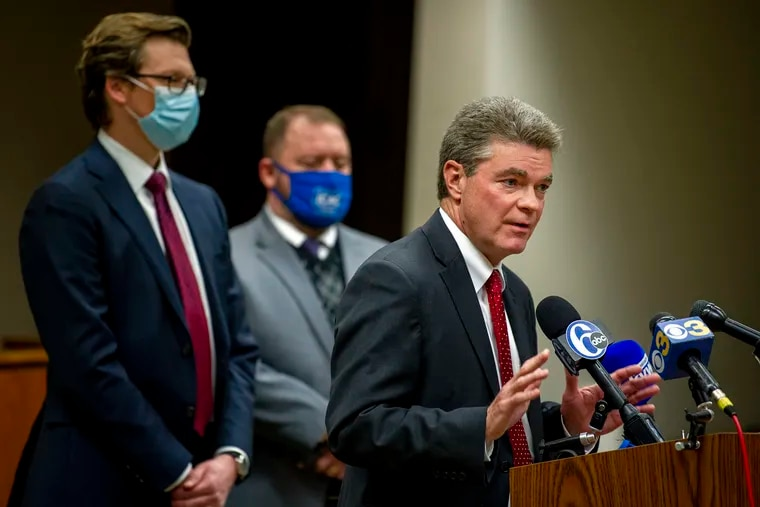 Delaware County District Attorney Jack Stollsteimer discusses charges filed against a man who cast an illegal vote for President Trump on behalf of a dead relative. Behind him are Douglas A. Rhoads (left), deputy of Investigation Unit, and Chief James E. Nolan IV, director of the Criminal Investigation Division.