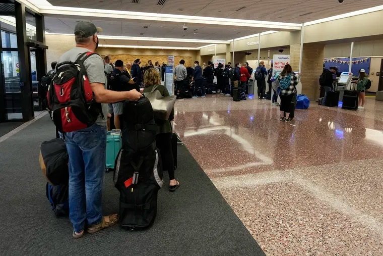 Passengers queue up at the ticketing counter for Southwest Airlines flights in Eppley Airfield Omaha, Neb., on Sunday.