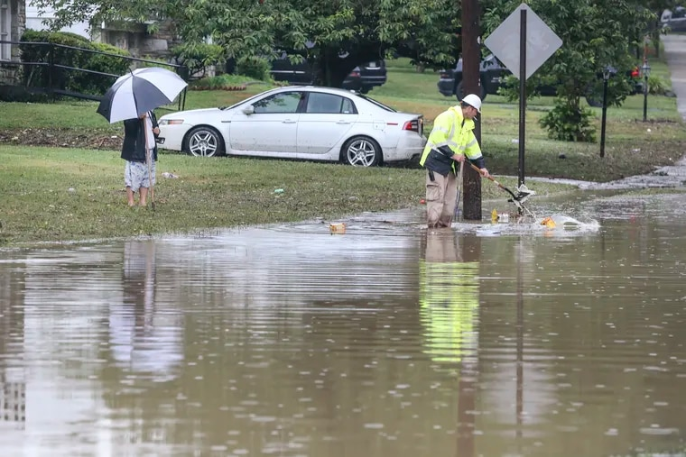 A Cheltenham Township worker tries to clear sewer on a flooded Coventry avenue near Stratford avenue as a neighbor watches, Monday, July 6, 2020