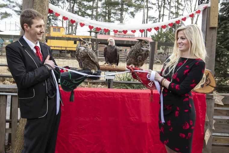 Elmwood Park Zoo educators Timothy Stephenson and Rebecca Oulton hold Sherlock, left, and Stella, right, as they tie the knot.