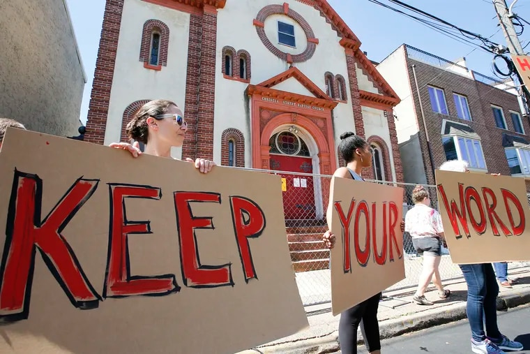 Aliza Schmidt (left), Charlette Caldwell (center) and Joni Lipson hold signs during a last-ditch protest attempt to stop the planned demolition of the Christian Street Baptist Church in the Bella Vista section of South Philadelphia on Saturday. The demolition is planned to start on Monday.