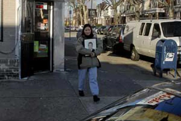 Jiaxhing's widow leaves the Lu family store today carrying her slain husband's portrait.