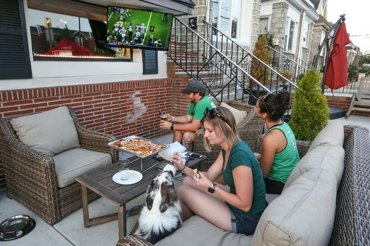 """Sitting outside at the Philadium, 1631 Packer Ave, Madison Hale feeds her dog """"Coal"""" sitting with Stephanie Lukas and Christian Ayres. Thursday, August 22, 2019"""