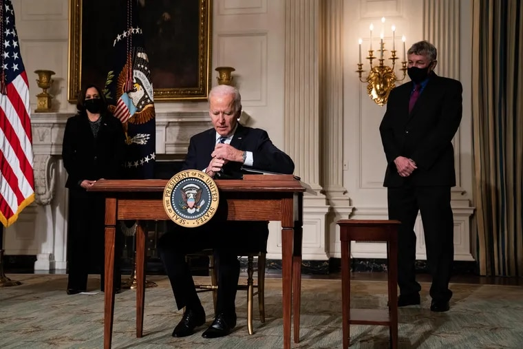 President Joe Biden signs executive orders after speaking about climate change issues at the White House on Wednesday. Also present are Vice President Kamala Harris (left) and White House science adviser Eric Lander.