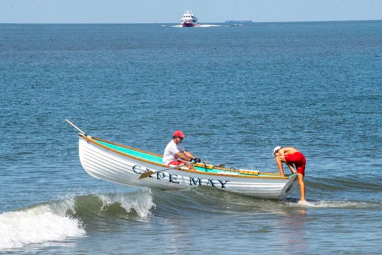 Cape May lifeguards paddle their surf boat against the waves last month.