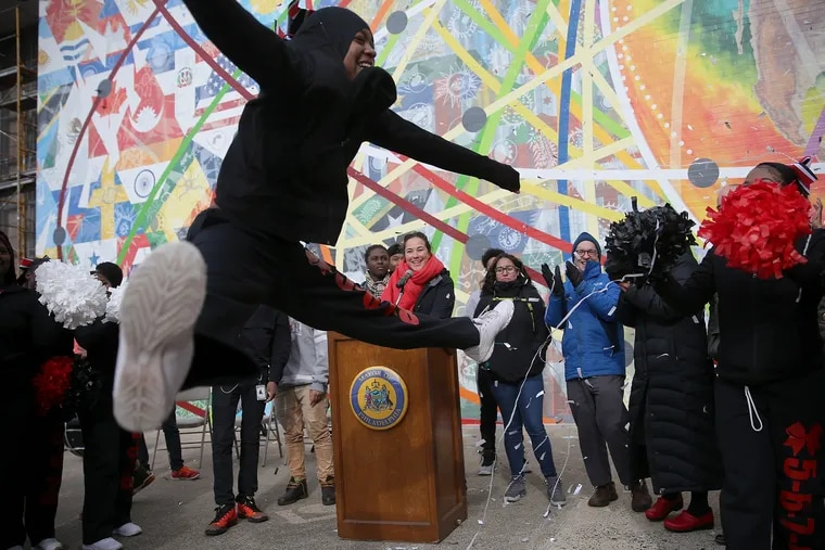 Cheerleader Najah Thomas, a senior, leaps as confetti falls to mark the dedication for a new mural at South Philadelphia High School.