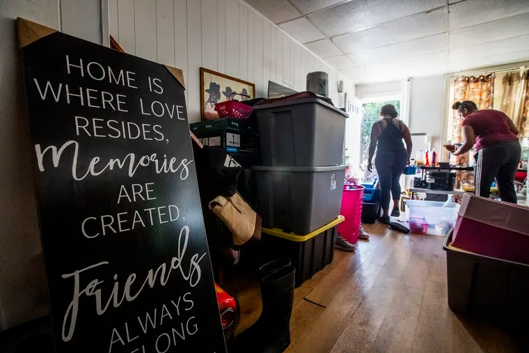 Antoinette Austin-Hunt, right and a friend work on cleaning and packing in her family's flood-damaged Bridgeport home on Sept. 7.