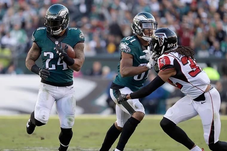 Ryan Mathews runs with the football as teammate Jordan Matthews blocks Falcons cornerback Jalen Collins.