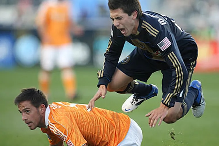 Michael Farfan grimaces after being upended by Houston's Danny Cruz during the first half. (Steven M. Falk/Staff Photographer)