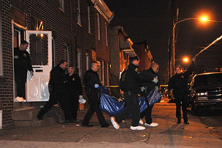 Philadelphia detectives carry the body of a woman from a house on C Street off of Somerset. It is not known if her death is connected to the Kensington strangler, but it is in the same area. (Sharon Gekoski-Kimmel / Staff Photographer)