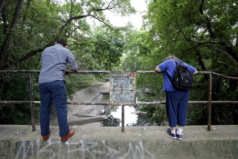Members of the Tookany/Tacony-Frankford Watershed Partnership peer over the wall of the combined sewer overflow, known as T8, in Tacony Creek Park in Philadelphia in 2019. The Philadelphia Water Department is planning to build a new $100 million wastewater pretreatment plant that will help it to reduce the volume of wastewater that flows into streams from combined sewer overflows.