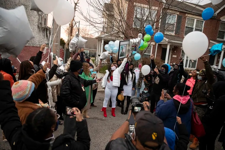 Tameka Porter (center) releases balloons in memory of seven people killed on Lex Street in 2000. It was the single worst mass killing in Philadelphia history.