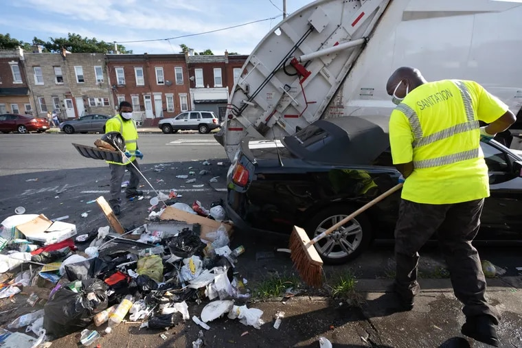Sanitation workers Rashan Purcell (left) and Lawrence Brown collect trash on Kensington Avenue in Philadelphia.