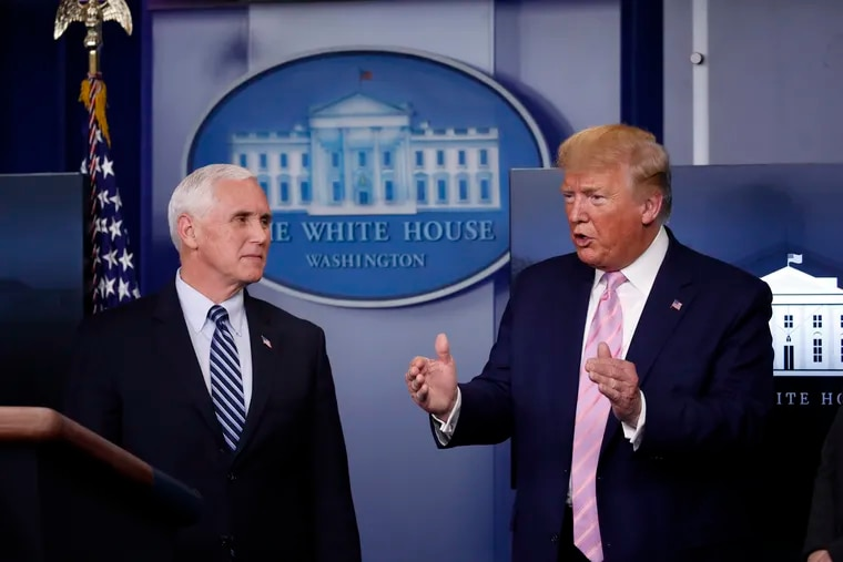 President Donald Trump speaks about the coronavirus as Vice President Mike Pence listens.