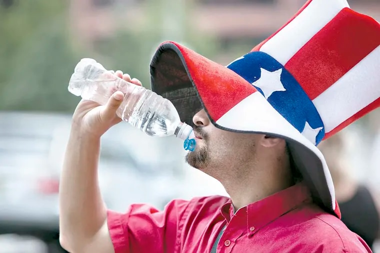 Eric Idelson, 22, of Richboro, takes a break from hawking tours on Independence Mall Sunday to hydrate himself with a bottle of water.