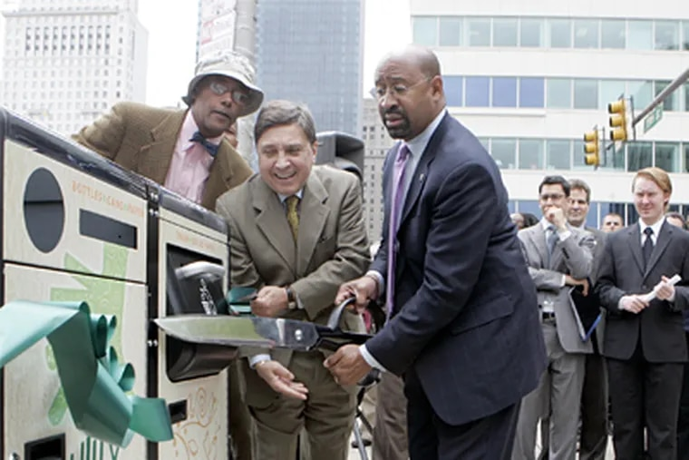 """Mayor Michael Nutter, along with Councilman Frank DiCicco and other officials illustrate the use of the new """"trash bins' at the NW corner of 15th and JFK in Philadelphia on Thursday afternoon. ( Bonnie Weller / Staff Photographer)"""