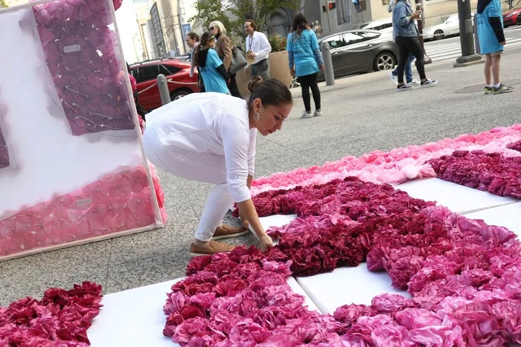 """Artist Michelle Angela Ortiz spells out """"Libertad"""" with paper flowers, meaning """"Freedom,"""" outside Philadelphia City Hall Wednesday during an artistic protest in 2017. Members of the Shutdown Berks Coalition have called on Gov. Wolf to shut down the detention center in Leesport."""