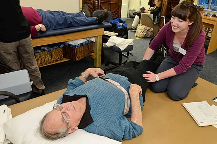 Courtney Christman, a physical therapy student at the clinic at Widener University, helps Bill Weir with a leg problem. The clinic, run by graduate students, is free to Chester residents. (Ron Tarver/Staff)