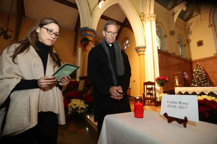 Lourdes Gonzalez-Sherby reads a prayer Saturday as Father Mike McCue lights one of 22 candles at a vigil at Cathedral of the Immaculate Conception to honor the homicide victims in Camden in 2017.  DAVID SWANSON / Staff Photographer