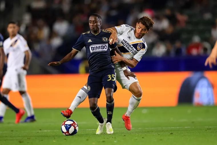 Philadelphia Union midfielder Jamiro Monteiro holds off Los Angeles Galaxy midfiedler Jonathan dos Santos during the Galaxy's 2-0 win at Dignity Health Sports Park in Carson, Calif.
