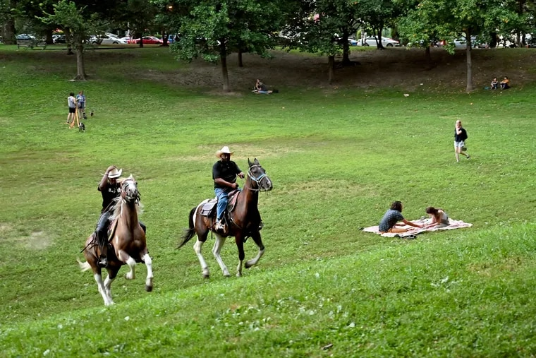 """August 2, 2021: Chris Coger (left) on Shadow and Malik Divers astride Big Sunny ride in Clark Park in West Philadelphia. Divers rides out of the brand-new Concrete Cowboys stables at Bartram's Garden. (He coined the term for his horse-riding program more than a decade ago, before the Idris Elba movie that took the same title rather than use that of the book, """"Ghetto Cowboy,"""" it was based on.)"""