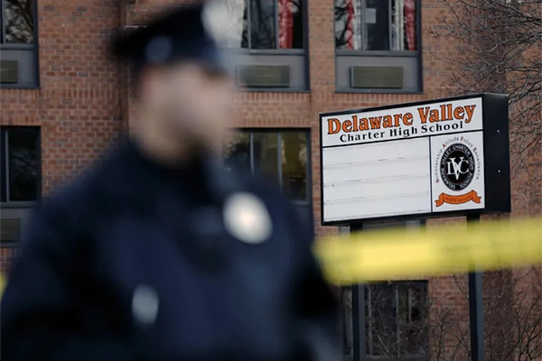 A police officer stands by caution tape at the Delaware Valley Charter School Friday, Jan. 17, 2014. (AP Photo/Matt Rourke)