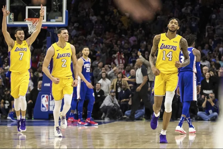 The Lakers' Brandon Ingram, right, reacts to hitting the winning basket along with Lonzo Ball, center, and Larry Nance Jr., left, against the 76ers Thursday night. Los Angeles beat the Sixers, 107-104