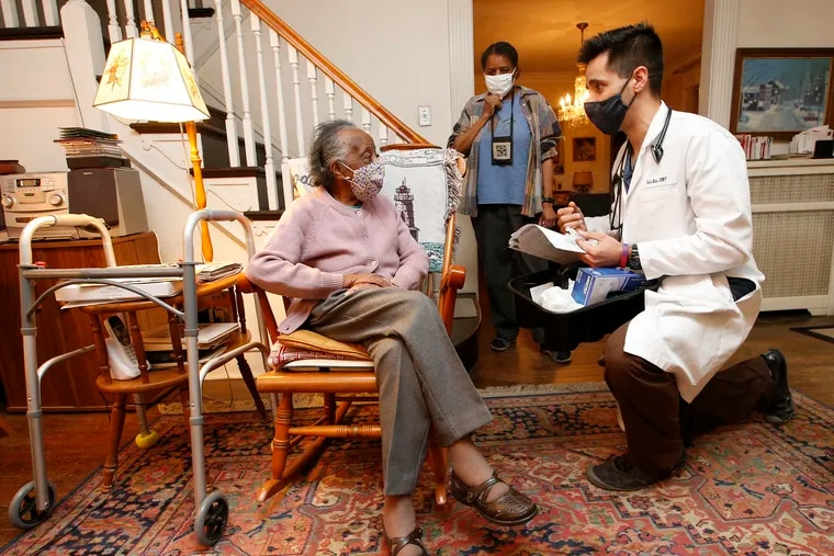 Nurse practitioner Tarik Khan talks to 101-year-old Jessie Birtha (left) with her 72-year-old daughter Becky Birtha listening before Khan administered leftover COVID-19 vaccine to the both of the women at their West Mount Airy home on Monday, March 8, 2021. Khan is from the Family Practice and Counseling Network.