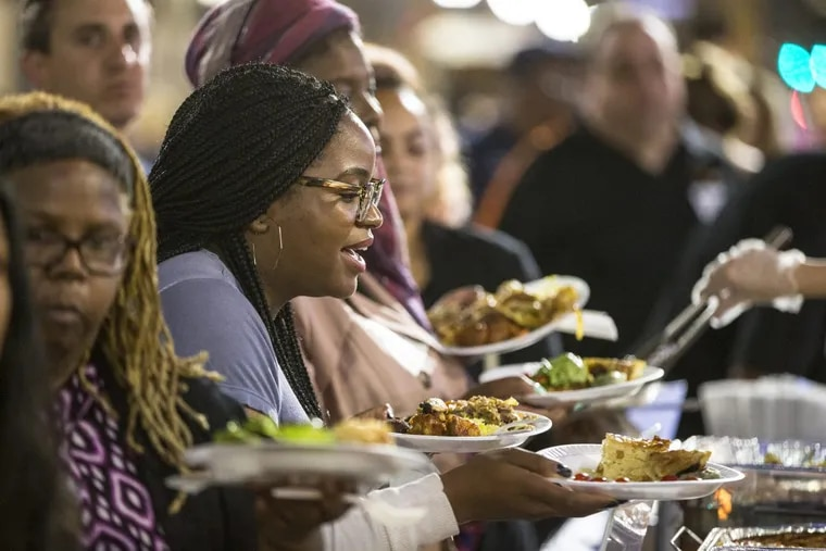 """Elizabeth Ayorinde  makes her way down the line of diverse cuisine that was available at the """"Breaking Bread, Breaking Barriers""""  dinner earlier this fall outside Reading Terminal Market."""