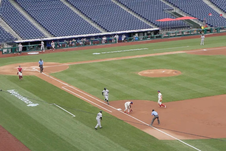 The Marlins' Jonathan Villar approaches first base after Phillies pitcher Vince Velasquez dropped the toss from Rhys Hoskins on Sunday.