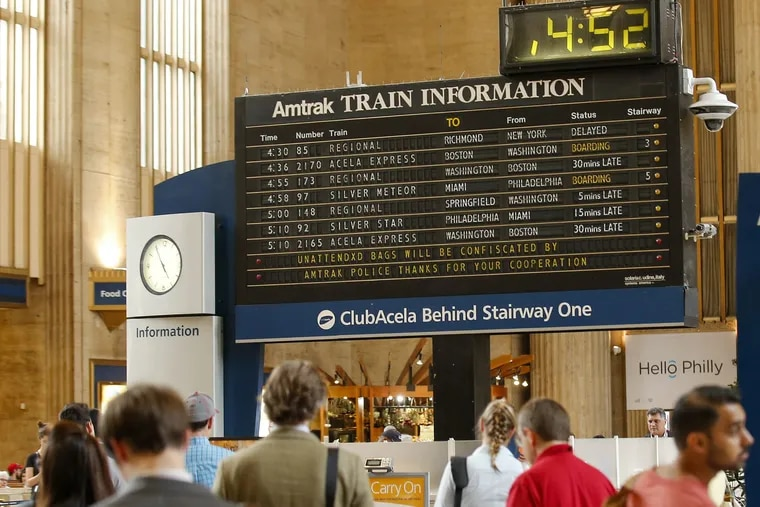 Amtrak riders at 30th Street Station stand near the train information board.