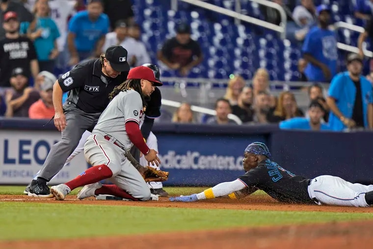 Miami's Jazz Chisholm Jr. slides safely into third base for a triple as Freddy Galvis is unable to hang on to the throw during a disastrous sixth inning for the Phillies on Friday.