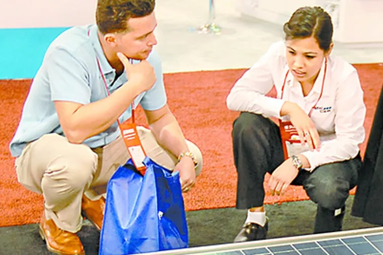 Next to a photovoltaic panel, Sunita Karmacharya of PanelClaw Inc. talks with Jimmy Rugova,a student at Bronx Community College's Center of Sustainable Energy, at the Convention Center. (Tom Gralish / Staff Photographer)