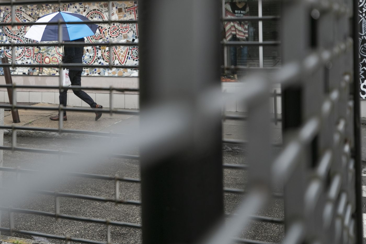 A pedestrian is seen through a closed shop at 5th and South Street on Saturday, March 28, 2020. A stay at home order has been issued in Philadelphia due to the spread of the coronavirus (COVID-19). All nonessential businesses are closed. Restaurants are now takeout or delivery only.