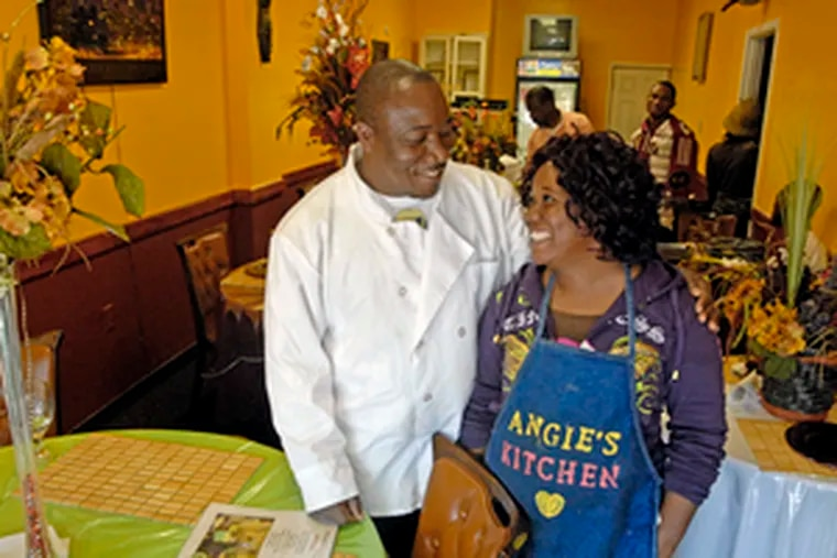 Augustine Manyeh, who runs Angie's Kitchen in the 600 block of South 52d Street, chats with his sister, Comfort Manyeh. Augustine Manyeh said he fears Liberia will not able to absorb all the refugees who will be forced to return.