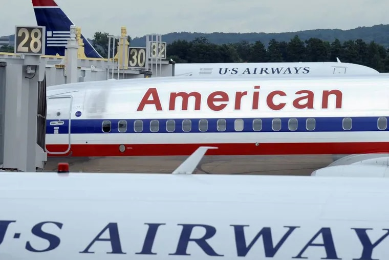 This Aug. 13, 2013 file photo shows an American Airlines plane between two US Airways planes at Washington's Ronald Reagan National Airport. American Airlines emerged from bankruptcyand US Airways culminated its long pursuit of a merger partner when the two completed their deal Dec. 9, 2013, creating the world's biggest airline.  (AP Photo/Susan Walsh, File)